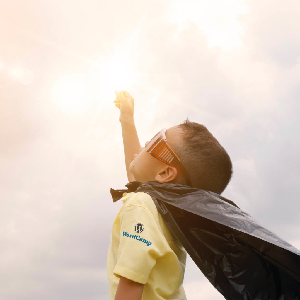 Boy wearing a plastic bag for a cape, with fist in air, looking up to a bright light.